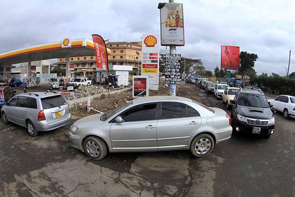 Coda di autoveicoli a una stazione di servizio nell'imminenza dell'aumento del costo carburante