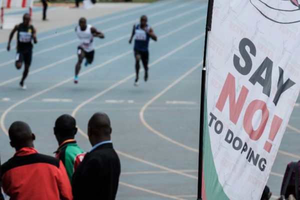 Athletes run as an anti doping banner is seen during the heat of the men's 100m at the Kenya National Trials at Kasarani Stadium in Nairobi on June 21, 2018, ahead of the 21st African Senior Championships in Nigeria to be held on August 1-5, 2018. / AFP PHOTO / Yasuyoshi CHIBA