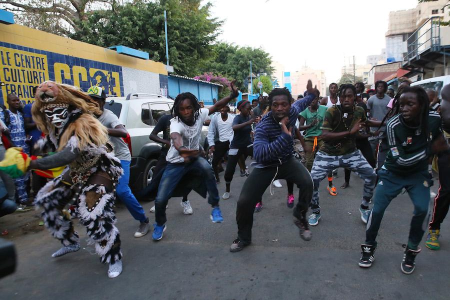 La foto della settimana e video. Camminando per le vie di Dakar, fra danze di strada e di falsi leoni