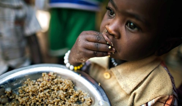 A child eating lentils in Rwanda