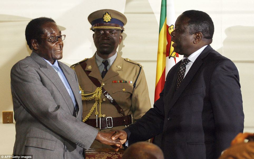 Zimbabwean President Robert Mugabe (left) shaking hands with Movement for Democratic Change leader Morgan