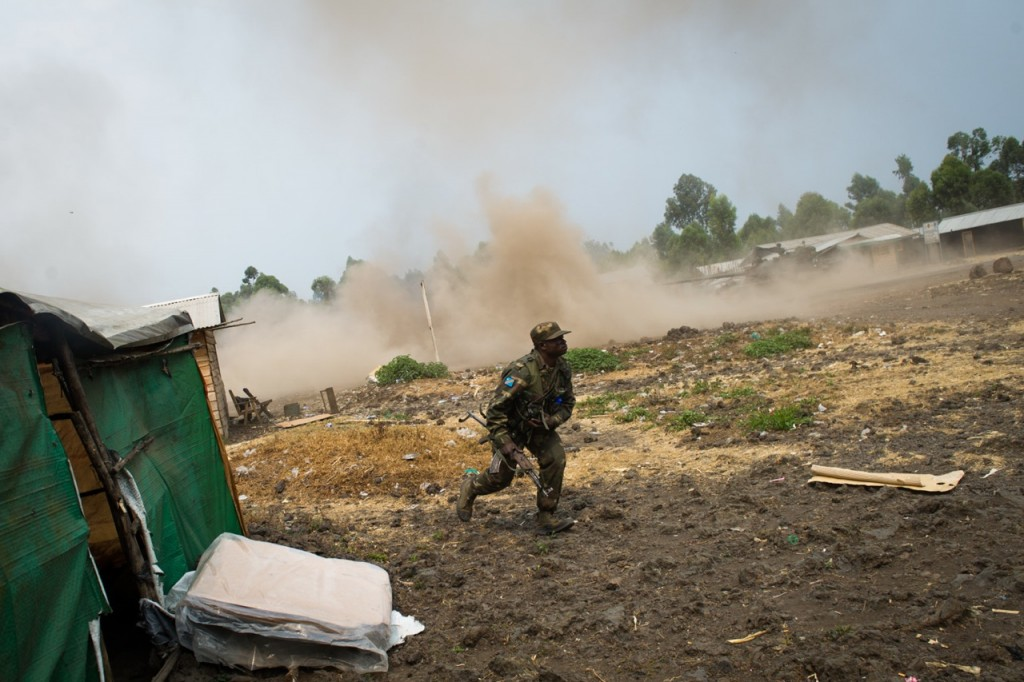 A Congolese army soldier reacts to shelling in the village of Kanyarucinya, on the outskirts of Goma, in the east of the Democratic Republic of the Congo on July 17, 2013. Heavy fighting erupted today between M23 rebels and the government forces. [PHIL MOORE]