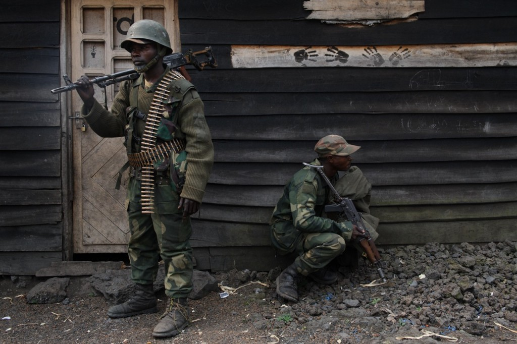 Congolese national army soldiers take cover beside a wooden shack during fighting between the army and M23 rebels on the outskirts of Goma in the east of D. R. Congo on July 17, 2013. For the first time in over a year, the army is gaining ground against the rebels, who took the city of Goma last November. [PHIL MOORE]