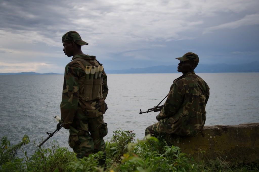 M23 rebels sit on the shore of Lake Kivu in the city of Goma in the east of the Democratic Republic of the Congo on November 20, 2012. Following gun fights with government soldiers this morning, the rebels walked through the city of Goma, and continued un-challenged to the Rwanda border, past United Nations peacekeepers. [PHIL MOORE]