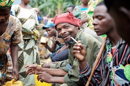 Militiamen and civilians drinking cassixe, banana beer, in the Lukweti market. August 2013. ALEXIS BOUVY/ Local Voices