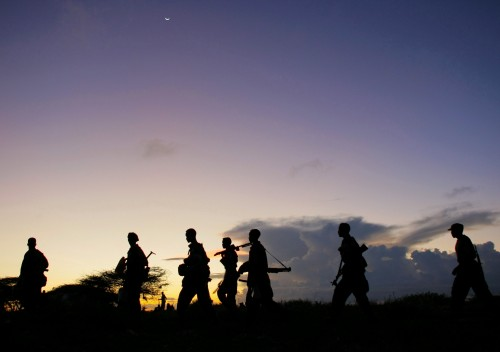 "Soldiers of the Somali National Army (SNA) walk at dusk under a rising crescent moon near the outskirts of Afgooye, a town to the west of Somali capital Mogadishu. On the third day of the SNA's joint offensive with the African Union Mission in Somalia (AMISOM), dubbed ""Operation Free Shabelle"", troops have advanced to almost two kilometres outside the strategically important town, having captured along the way swathes of territory previously under the control of the Al Shabaab insurgent group. Photo ID 515019. 24/05/2012. Somalia. UN Photo/Stuart Price."
