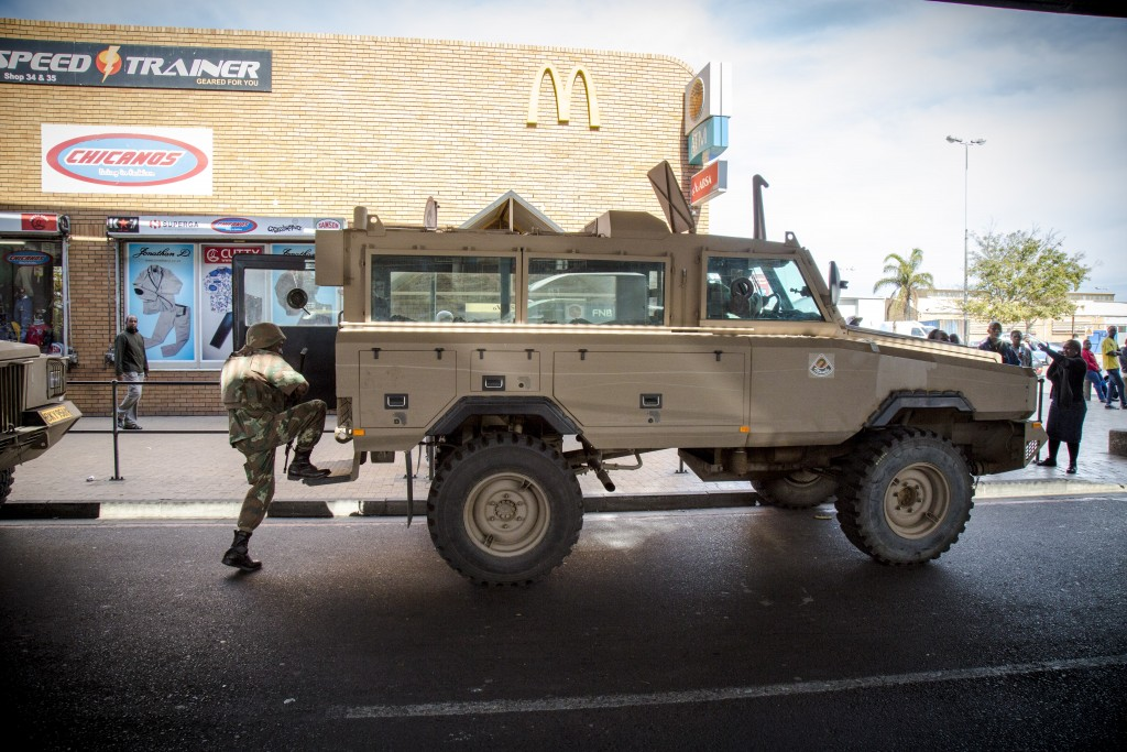 An SANDF soldier climbs aboard one of his unit's Mamba armoured personnel carriers during a police-led cordon and search operation in Bellville, Western Cape. TRENT PERKINS/ADR