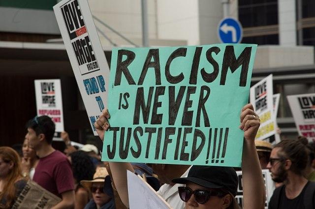 """Cartellone con scritta in inglese """"Il razzismo non è mai giustificato"""""""