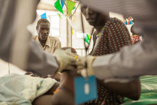 """In primo piano: Nyaniema Gatluak e il suo bambino PY malato di polmonite. """"Siamo venuti qui a causa dei combattimenti. C'erano spari giorno e notte, così siamo scappati per raggiungere il campo"""", ha raccontato Gatluak. Sullo sfondo, Peter Gatkoth, che ha portato la figlia in ospedale. """"È come se non fossimo mai nati. Non abbiamo più nulla. Né bestiame né coltivazioni"""", ha detto Peter Gatkoth, padre di Nyaga Gatkoth, 5 anni, ricoverato presso l'ospedale di MSF nel POC di Bentiu per una grave malaria. """"Siamo arrivati a maggio dopo che il nostro bestiame è stato depredato e le nostre case bruciate. Se ci avessero trovato, avrebbero bruciato anche noi"""", ha detto Gatkoth. Foto di Brendan Bannon. POC di Bentiu, Sud Sudan. Settembre 2015."""