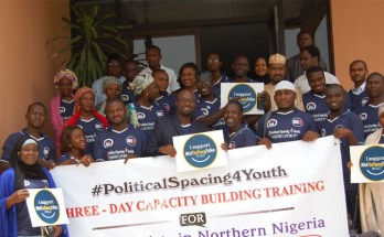 Youth trainees pose for a group photo shortly after the training, displaying placards supporting the #NotTooYoungToRun campaign