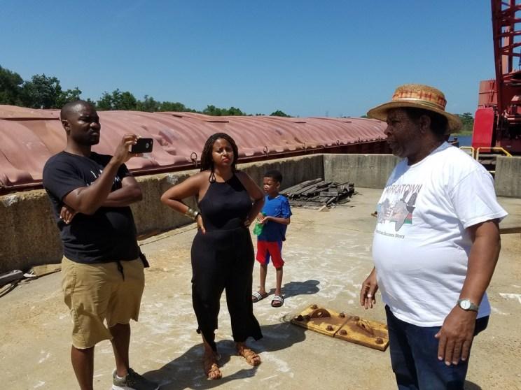 Womack explains the history of Hog's Bayou to the Africatown community