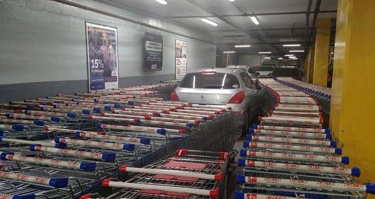 Photo of Man parks wrongly after which his car is enclosed by shopping trolleys