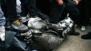 Photo of British protesters draw statue of slave trader from plinth and throw it into water