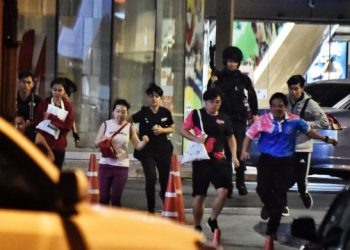 People run together as they are rescued by Thai commandos from Terminal 21 shopping mall, where a mass shooting took place, on February 9, 2020 in the Thai northeastern city of Nakhon Ratchasima. (Photo by Lillian SUWANRUMPHA / AFP)