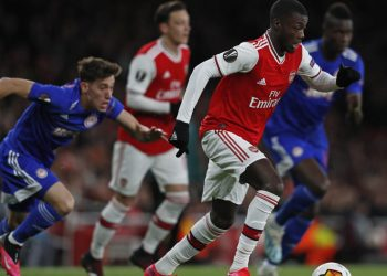 Arsenal's French-born Ivorian midfielder Nicolas Pepe (R) runs with the ball during the UEFA Europa league round of 32 second leg football match between Arsenal and Olympiakos at the Emirates stadium in London on February 27, 2020. (Photo by Adrian DENNIS / AFP)