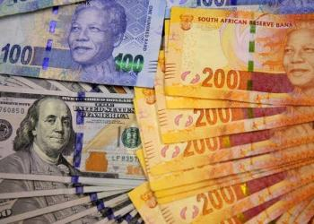 South African bank notes featuring images of former South African President Nelson Mandela (R) are displayed next to the American dollar notes in this photo illustration in Johannesburg, file. REUTERS/Siphiwe Sibeko