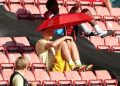 Arsenal's German midfielder Mesut Ozil (C) shelters from the sunshine beneath an umbrella during the English Premier League football match between Southampton and Arsenal at St Mary's Stadium in Southampton, southern England on June 25, 2020. Andrew Matthews / POOL / AFP