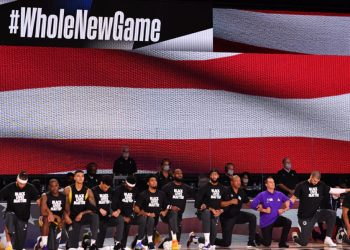 Orlando, FL – JULY 30: The Los Angeles Lakers and the LA Clippers kneel during the National Anthem prior to a game on July 30, 2020 at The Arena at ESPN Wide World Of Sports Complex in Orlando, Florida. NOTE TO USER: User expressly acknowledges and agrees that, by downloading and/or using this Photograph, user is consenting to the terms and conditions of the Getty Images License Agreement. Mandatory Copyright Notice: Copyright 2020 NBAE Jesse D. Garrabrant/NBAE via Getty Images/AFP