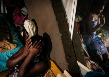 Linet (L), 16, who is around 3 months pregnant covers her face with a hand during an interview for AFP with her sister Carol (in mirror), 22, about Linet's unexpected pregnancy as schools are closed due to the COVID-19 outbreak, at her sister's home in Raila slum, next to Kibera slum, in Nairobi, on July 15, 2020. – Linet is one of thousands of teenagers who fall pregnant every year in Kenya, a problem experts fear is worsening during the coronavirus pandemic, with some girls pushed into transactional sex to survive while others have more sex as they stay home from school. For many girls like Linnet, hopes of ever returning to school will be fully dashed once they give birth. (Photo by Yasuyoshi CHIBA / AFP)