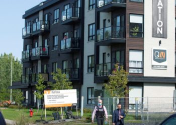 Police investigators walk past a condo building related to an investigation into the ricin-filled envelope sent to the White House, as the Royal Canadian Mounted Police (RCMP) Chemical, Biological, Radiological, Nuclear, Explosives team checks the area in Longueuil, Quebec, Canada September 21, 2020. REUTERS/Christinne Muschi