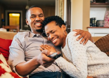 Couple loved up in front of a TV Photo – Getty Images