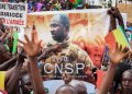FILE - In this Sept. 8, 2020 photo, people hold a banner showing Col. Assimi Goita, leader of the junta running Mali, as they demonstrate to show support for the junta in Bamako, Mali.