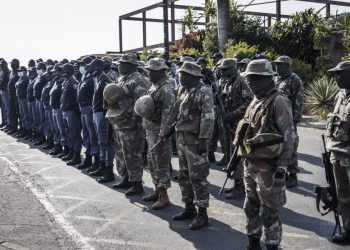 South African National Defence Forces (SNADF) soldiers and South Africa Police Services (SAPS) members line up in front of the Phoenix Police Station in Durban, on July 21, 2021, where a delegation of interfaith leaders led by Bishop Bishop Vusi Dube met with police commanders to demand the police to investigate the killing of over 20 Black South African allegedly at the hands of vigilante groups. - Phoenix is a flashpoint town between black South Africans and counterparts of Indian origin where at least 20 people died in the recent wave of violence. Like communities across South Africa, residents of the predominantly ethnic Indian town set up their own protection squads in response to pillaging and arson that broke out days after the jailing of ex-president Jacob Zuma on July 8th -- overwhelming security forces. (Photo by MARCO LONGARI / AFP)