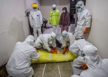 This picture taken on July 6, 2021 shows a handling team wrapping the body of a Covid-19 patient, who died at home during self-isolation after the local hospital was unable to accommodate further coronavirus patients, in Bogor, West Java. (Photo by ADITYA AJI / AFP)