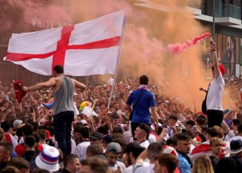 (FILES) In this file photo taken on July 11, 2021 England fans cheer on their team outside Wembley Stadium ahead of the UEFA EURO 2020 final football match between England and Italy in northwest London. – England must play their next home match in a UEFA competition behind closed doors following disorder at the Euro 2020 final at Wembley, European football's governing body ruled on October 18, 2021. The showpiece game between England and Italy on July 11 was marred by chaotic scenes as ticketless supporters forced their way through security cordons to gain entry to the stadium. (Photo by Niklas HALLE'N / AFP)