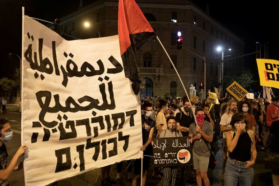 "Protesters holding a ""Democracy for all"" sign in Arabic and Hebrew"