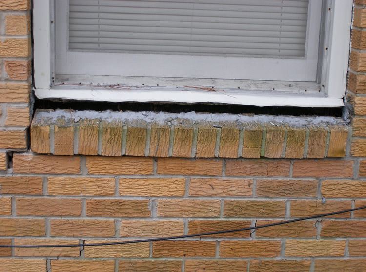 A window that is cracked at the corner and separating from the brick foundation wall in Bessemer