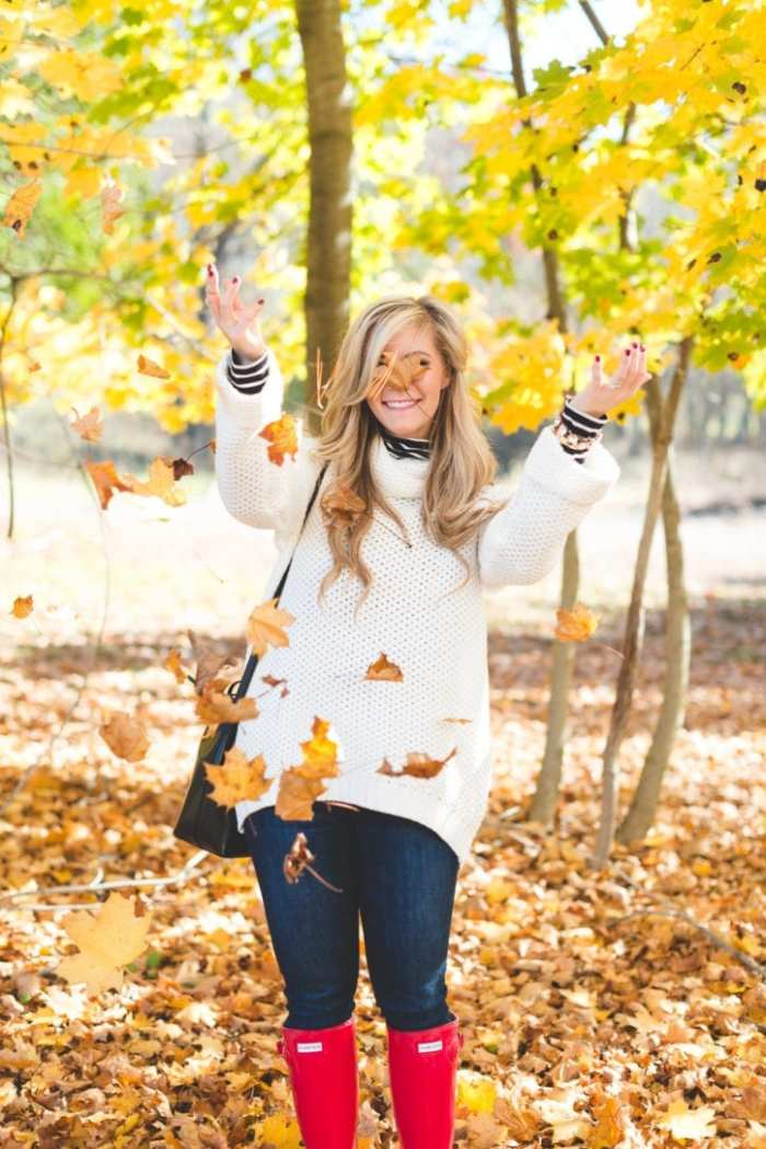 Blogger Ashley Pletcher enjoys playing in the leaves with this cozy fall look featuring the iconic Hunter boots , Mansur Gavriel Bag,