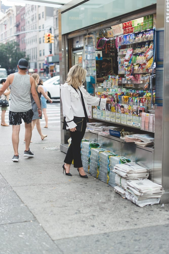 Blogger, Ashley Pletcher browses a newsstand for the latest celebrity gossip wearing an Asos ruffle top with Express pants and Jimmy Choo Pumps!
