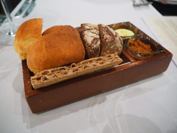 Freshly baked bread served with butter and tomato pesto