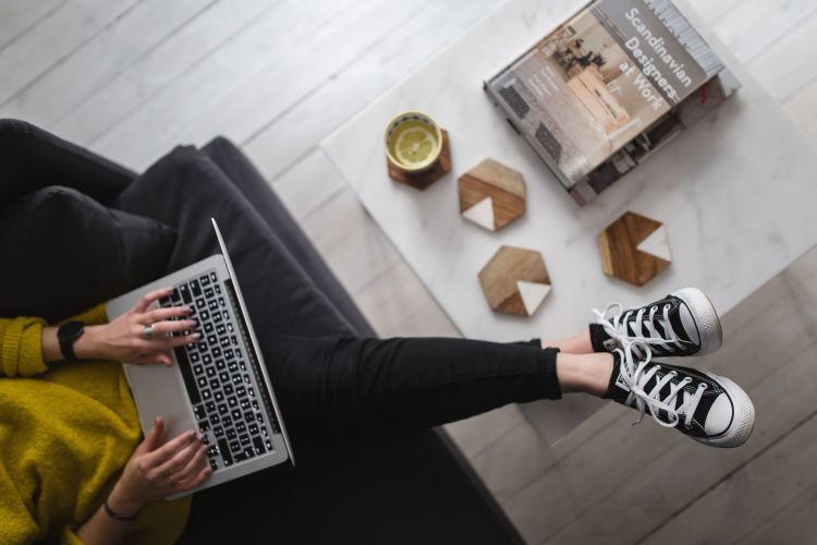 Seren network - Woman-with-legs-on-the-coffee-table-wearing-converse-sneakers-and-working-on-her-laptop