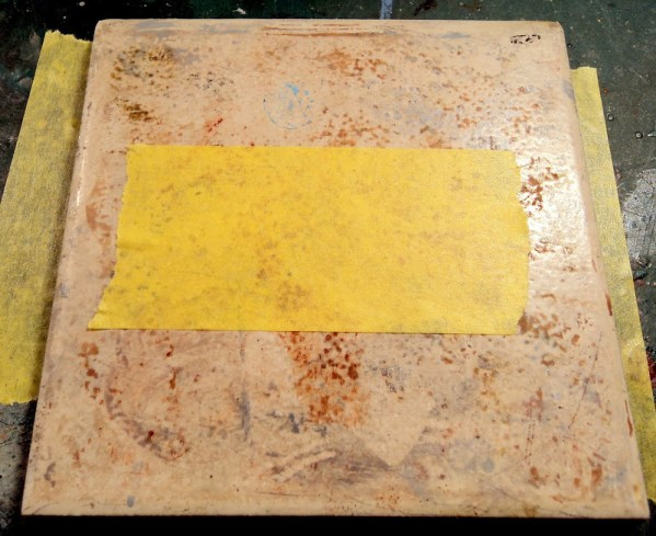 First, I'll put some masking tape down on on a piece of ceramic tile. using ceramic tile gives a good, hard, smooth cutting surface, and it can be easily rotated around for cutting curves.