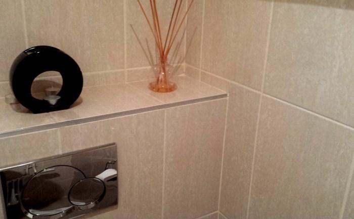 Pose de carrelage sur murs dans des toilettes