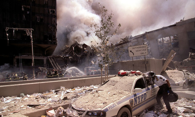 1074px-Rescue_worker_reaching_into_a_New_York_Police_car_covered_with_debris_(28802606564)