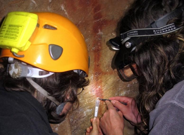 Los investigadores Dirk Hoffmann y Alistair Pike toman muestras de una costra de calcita en la parte superior del signo escalariforme rojo en La Pasiega /  J. Zilhão