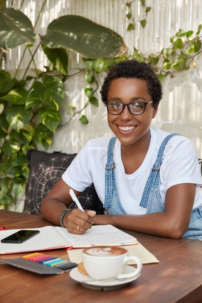 Photo of cheerful black woman being busy with diary writing or making business plan, enjoys hot beve