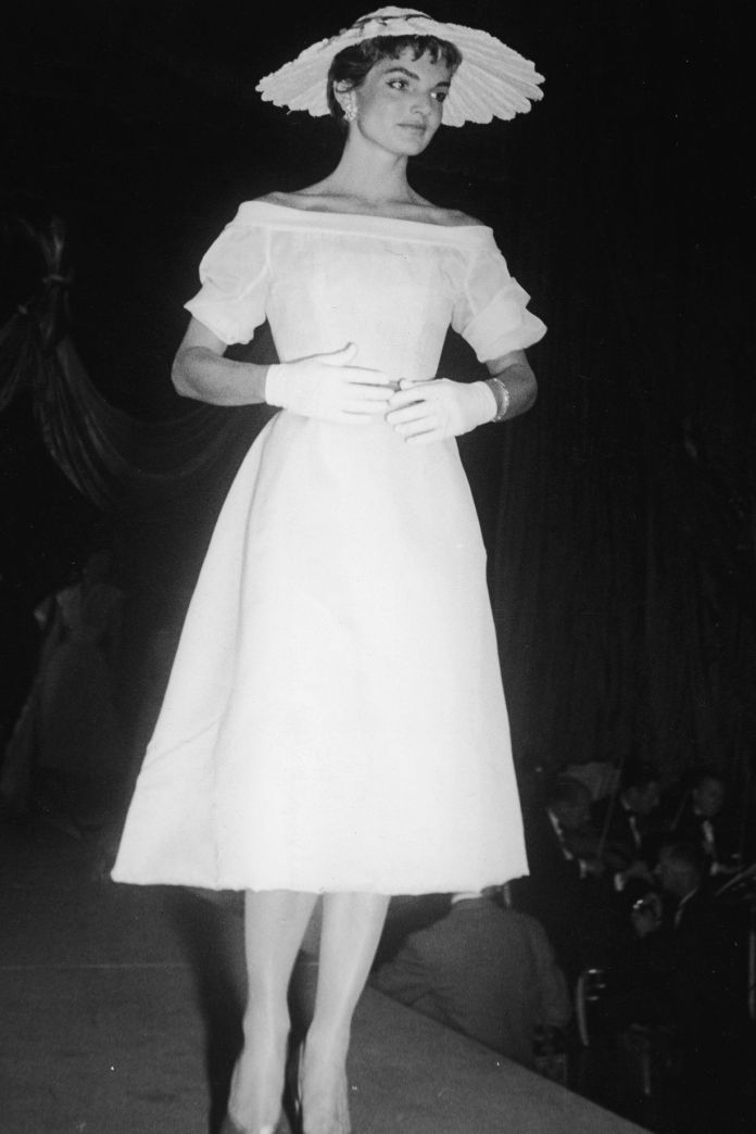 1954 All-white was a theme for Mrs. Kennedy, shown here in a white hat and another boat neck. Those white gloves finish the elegant idea.