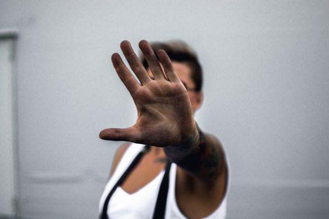 """Ein Mann streckt dem Betrachter die flache Hand entgegen um """"Stopp"""" zu signalisieren"""