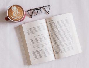 Buch neben Brille und Tasse Kaffee