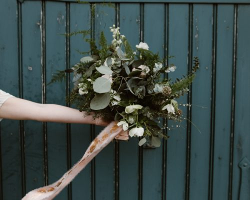 a shot of an arm holding out a green and blush pink bouquet - BOHEMIAN WEDDING ELSECAR HERITAGE CENTRE