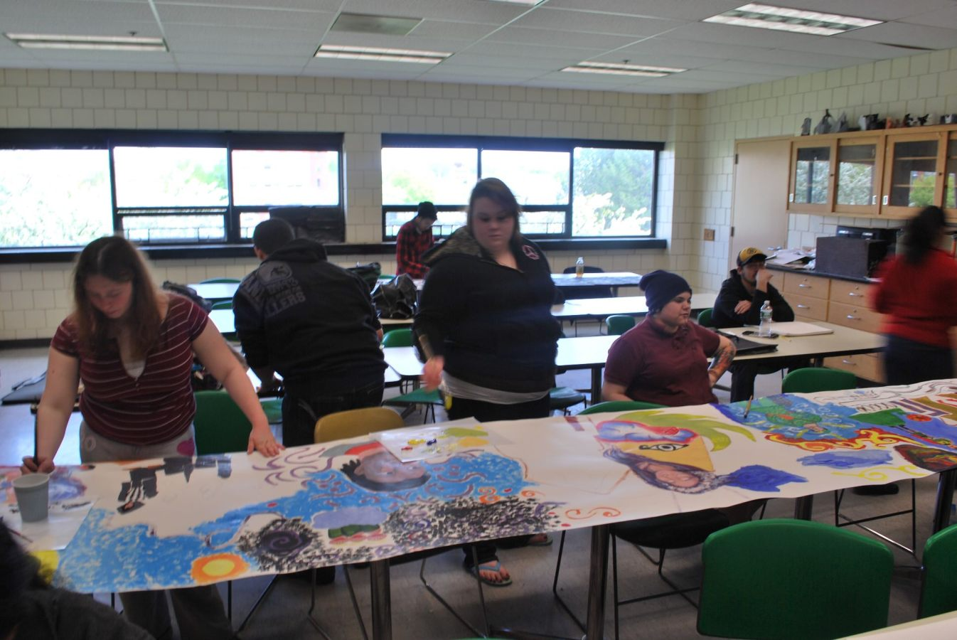 The class continues to color the mural