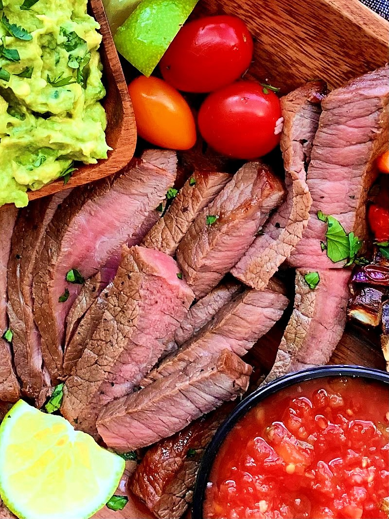 close up of medium rare sliced steak on a wooden board with guaramole and salsa