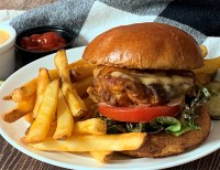 breaded chicken sandwich on a bun with french fries