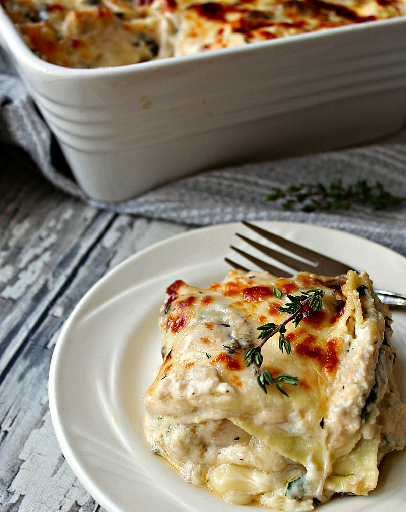chicken alfredo lasagna on white plate with casserole dish in background