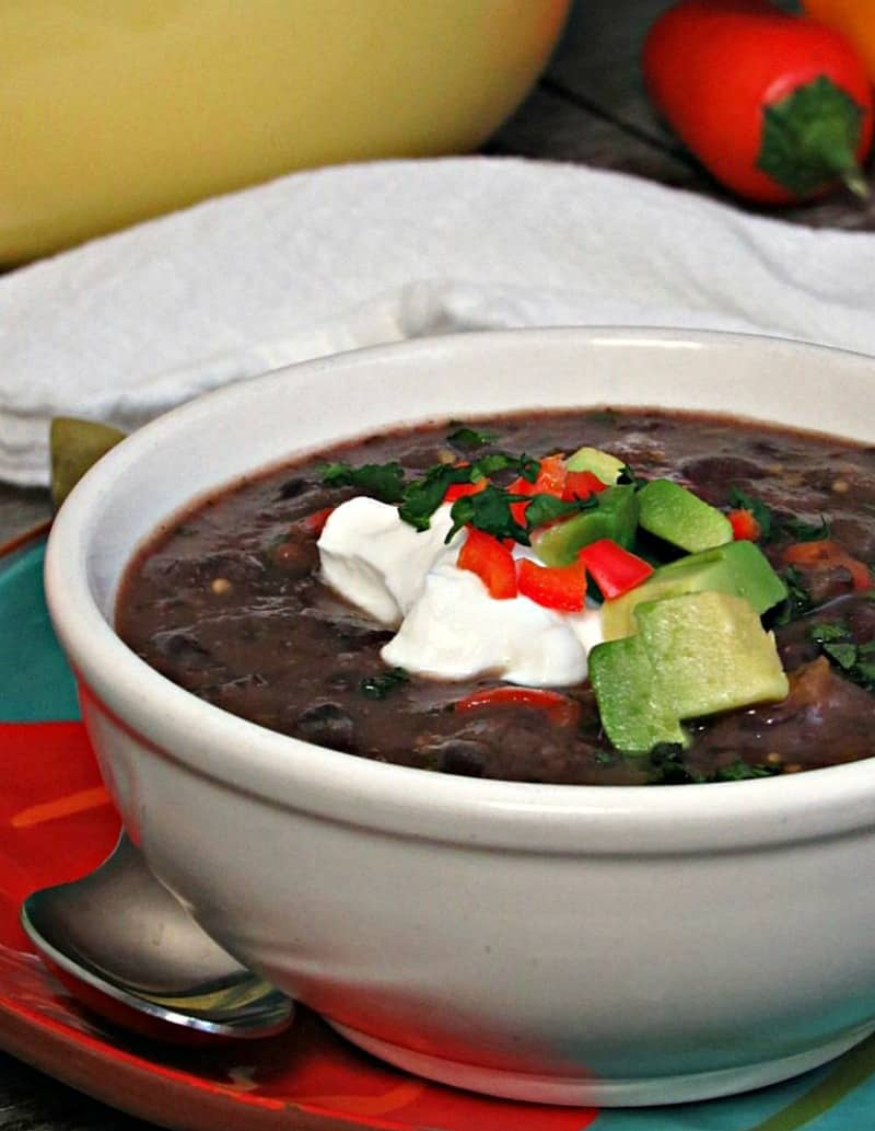 bowl of black bean soup garnished with sour cream and avocado