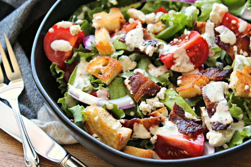 black bowl with BLT Salad drizzled with ranch dressing